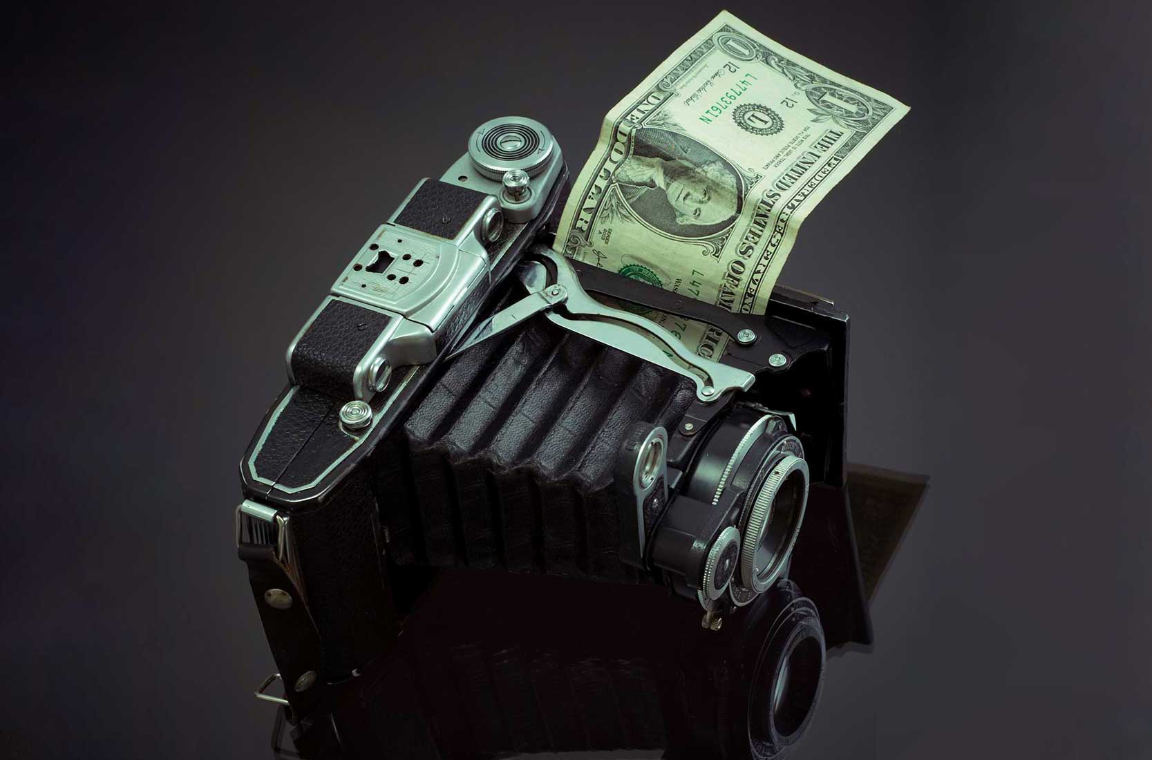 Vintage camera with a dollar bill sticking out