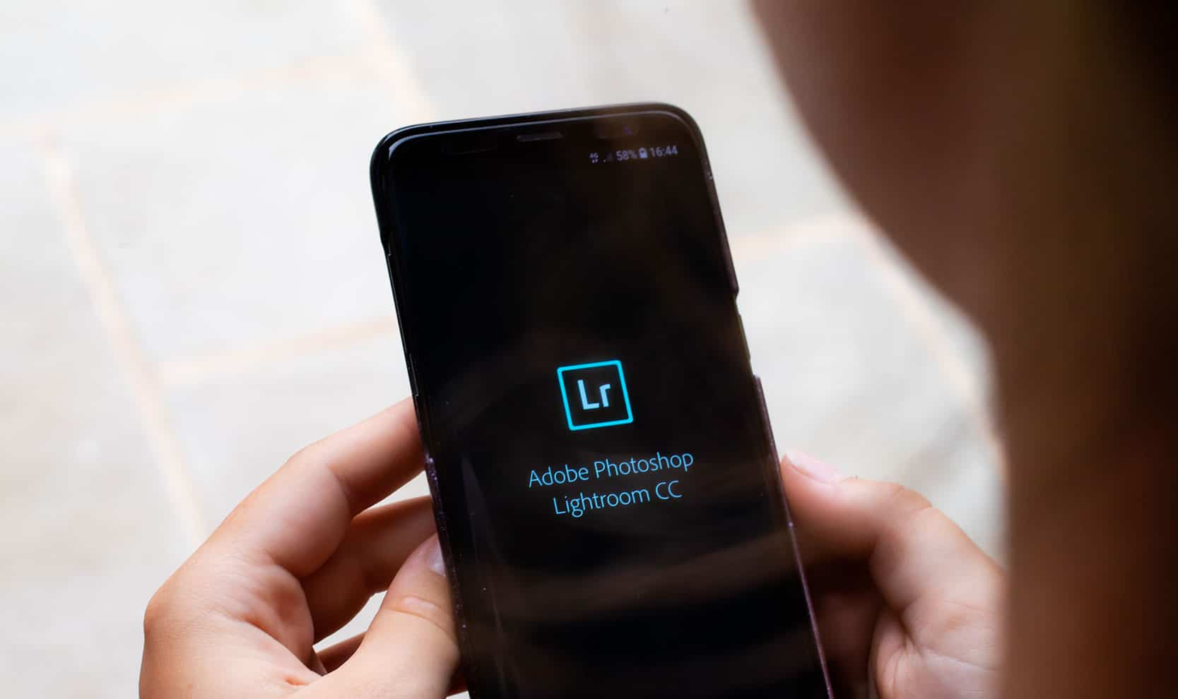 Lightroom CC load screen, a user opening Lightroom app on a smartphone.