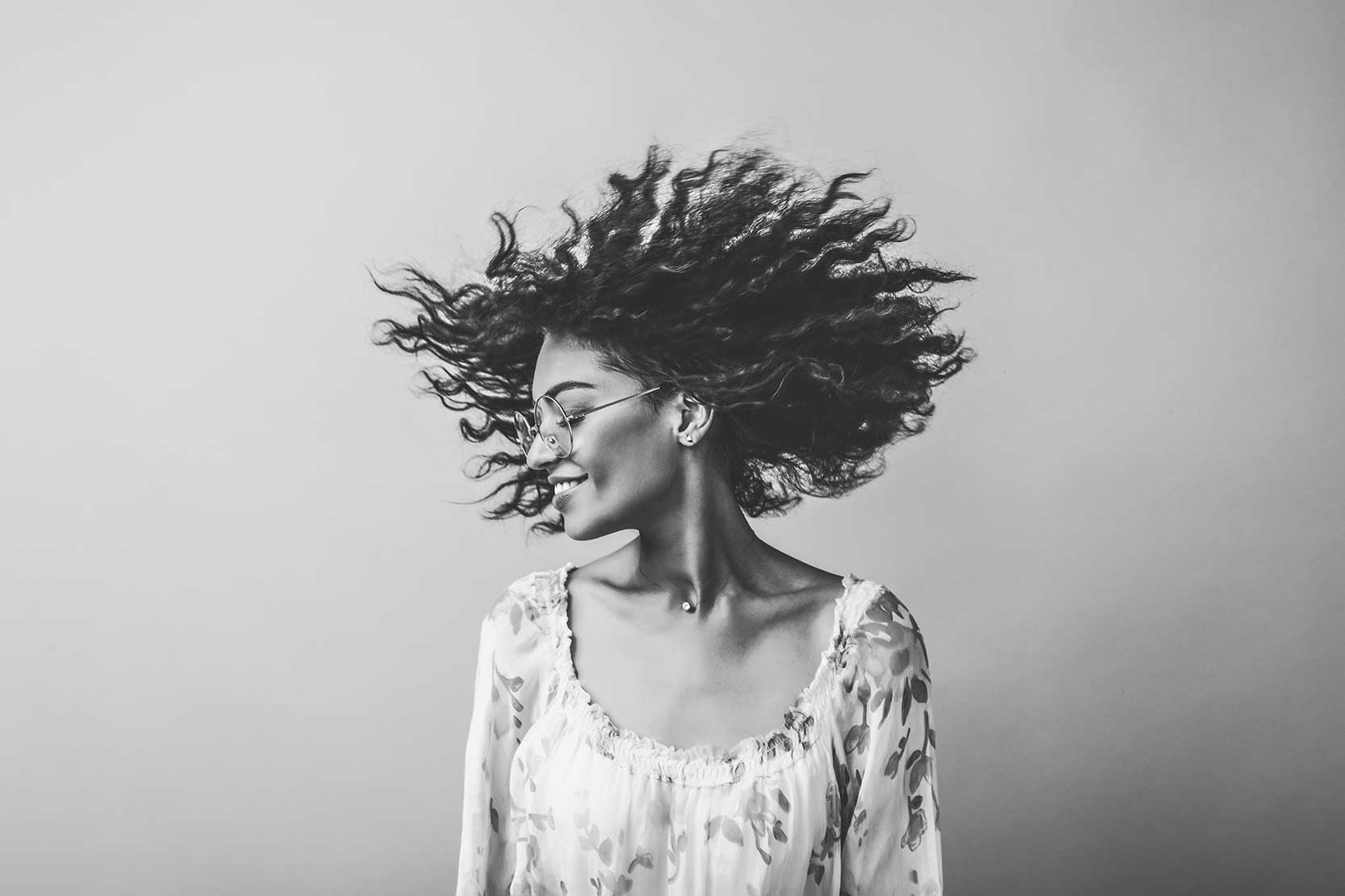 Portrait of a woman, hair blowing through the wind. Black and white preset.